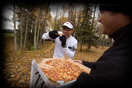 Runner eating pizza during a marathon in Anchorage, Alaska.